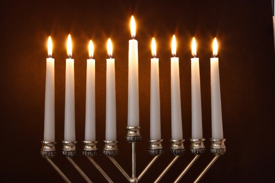 A hanukiah has 9 candles, one of which is at a different height than the others.